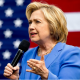 Hillary speaking in front of American Flag