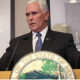 Pence speaking above Indiana seal