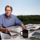 Charlie Rose on patio with newspapers