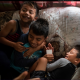 Alex Galvez, 12, center, plays with his second cousins in his family's mobile home in Norwalk