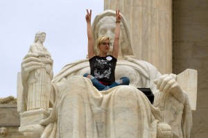 Protestor sits on a statue on the steps of the Supreme Court